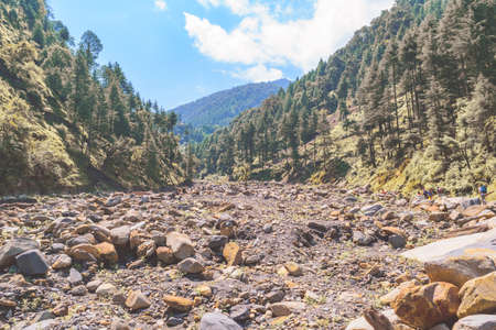 View enroute to Prashar Lake trekk trail through river bed. It is located at a height of 2730 m above sea level surrounded by lesser himalayas peaks near Mandi, Himachal Pradesh, India.