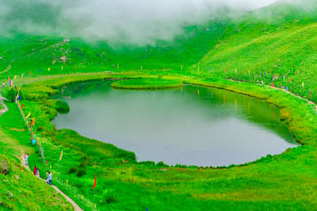 View at Prashar Lake located at a height of 2730 m above sea level with a three storied pagoda-like temple of sage Prashar near Mandi, Himachal Pradesh, India. The lake has a floating island in it.