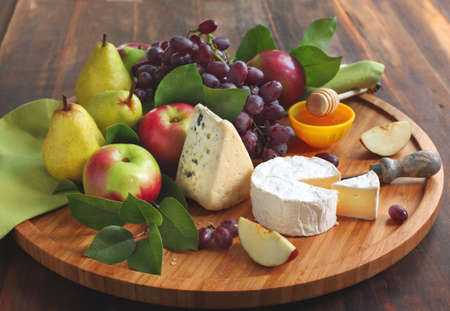 Cheese board with fruits and honey