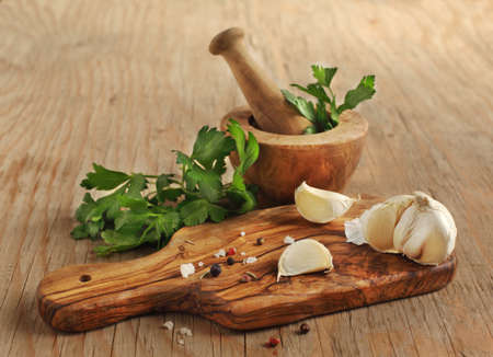 Garlic, parsley and spices on a cooking wooden board  版權商用圖片
