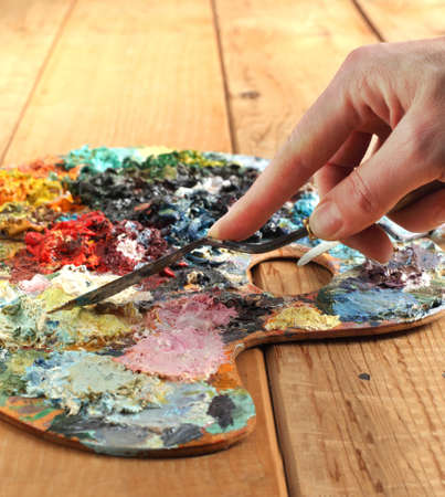 Hand with palette-knife and palette Stock Photo