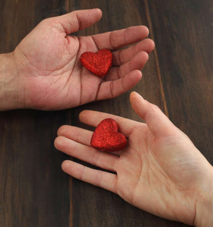 Men s and women s hand with a red heart photo