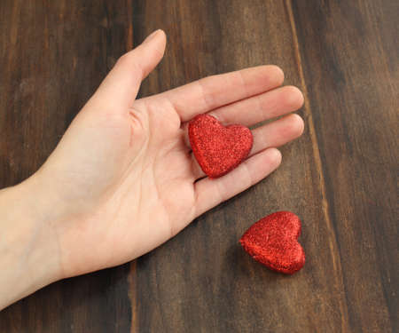 Women s hands with a red heart photo
