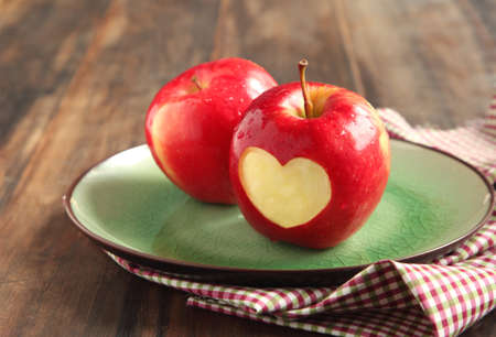 Red apple with a heart shaped cut-out photo
