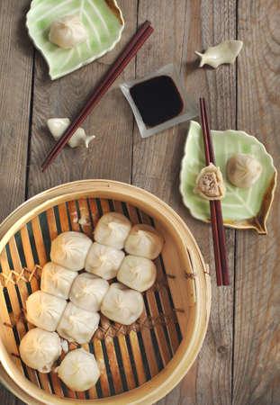 Chinese steamed pork buns in bamboo steamer basket
