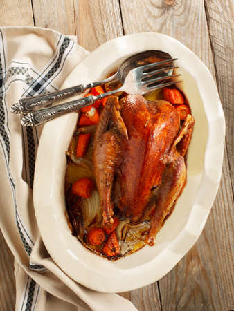 Baked pheasant in red wine with carrot and onion