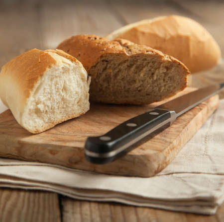 Whole grain bread and white bread on wooden chopping board  Selective focus photo