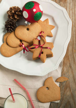 Christmas gingerbread cookies with festive decoration on the plate and glass of milk