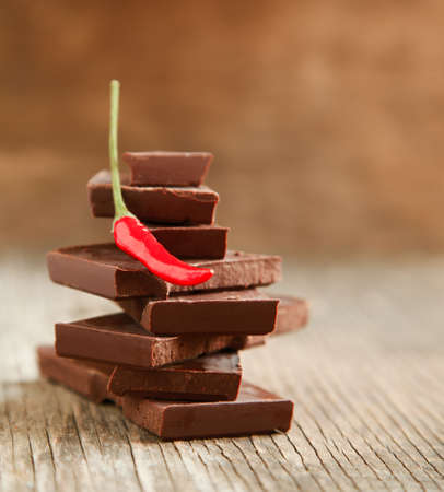 red chili pepper: Red chili pepper on stack of dark chocolate pieces on wooden background Stock Photo