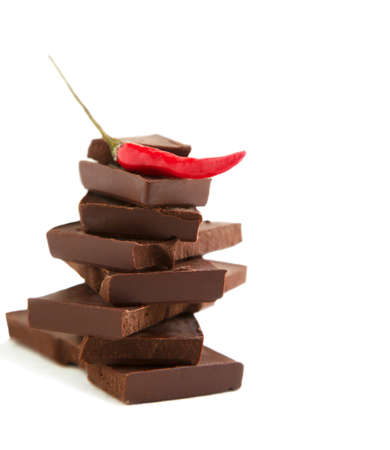 Red chili pepper on stack of dark chocolate pieces isolated on white background photo