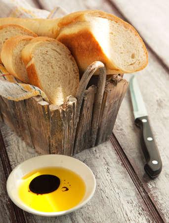 canasta de panes: Pan francés baguette corte a bordo de madera de pan y aceite de oliva Enfoque selectivo