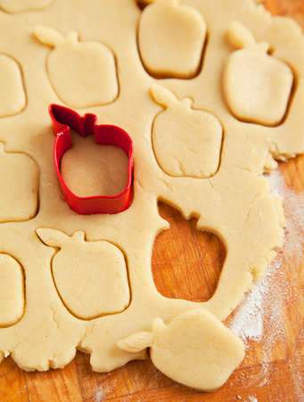 wood cutter: Apple shaped cookie cutter on raw cookie dough  Selective focus