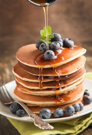 Stack of pancakes with fresh blueberry and maple syrup photo