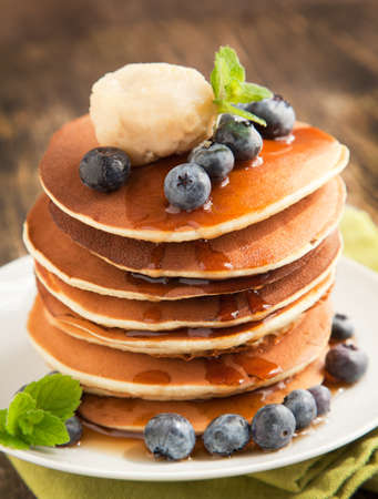 Stack of pancakes with fresh blueberry,maple butter and syrup photo