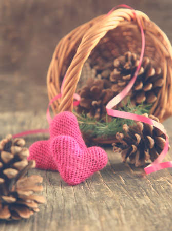 Pine cones and handmade crochet hearts in basket photo