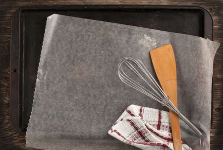 Old metal baking pan with paper and kitchen utensils photo