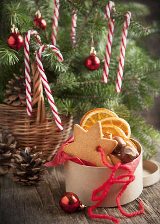 Green Branches of Fir with Christmas Decorationin in Basket and gift box with gingerbread cookie photo