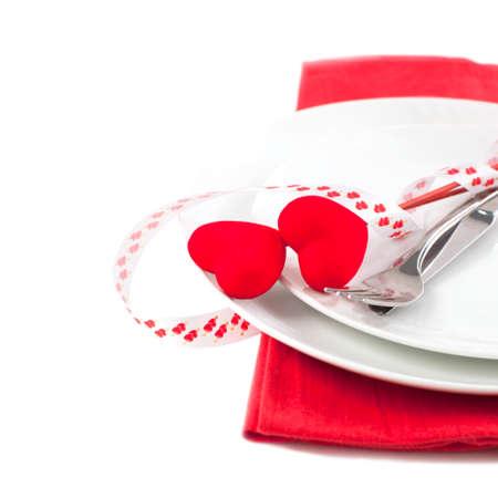 フォーク、ナイフおよび心の分離の白い背景でバレンタインの s 日のお祝いテーブルの設定