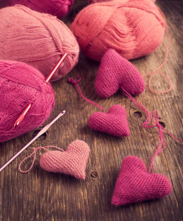 Crochet pink hearts  and yarn on wooden
