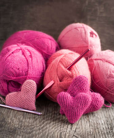 Crochet pink hearts  and yarn on wooden  photo