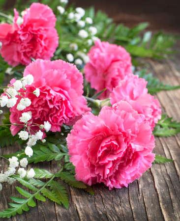 在木背景的桃红色康乃馨