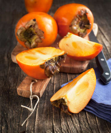persimmons: Fresh ripe persimmons on a wooden table