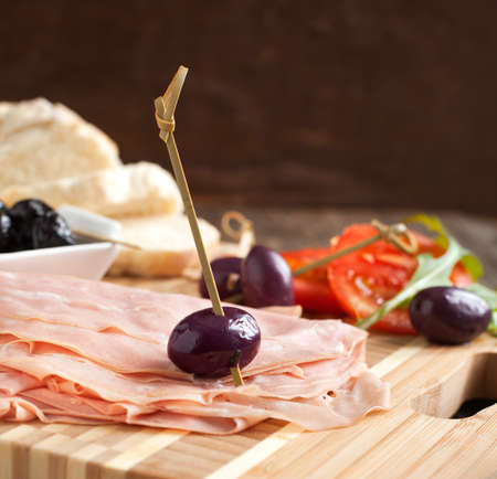 Sliced mortadella on wooden cooking board with bread, tomato and olives