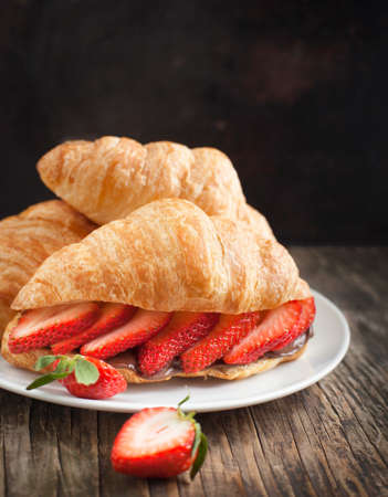 Fresh croissants with strawberry and chocolate nuts cream photo