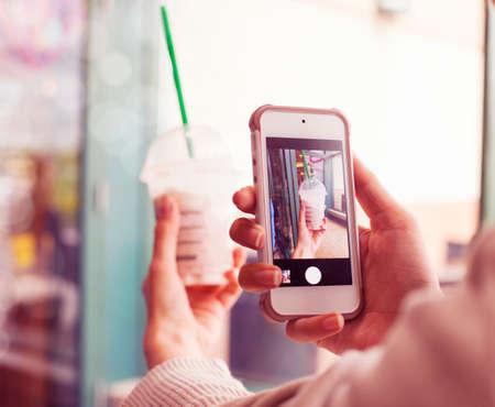 foto: Close-up maken van een foto van een kopje frappuccino mobiele telefoon Gestemd beeld met