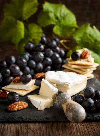 Delicious cheese crackers appetizer with grapes and pecans on cooking board. Imagens