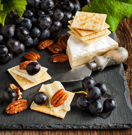 Delicious cheese crackers appetizer with grapes and pecans on cooking board. photo