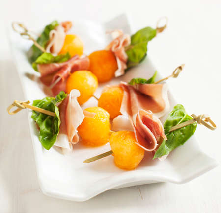 holiday catering: Appetizer with melon and prosciutto on skewers