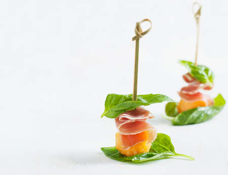 Appetizer with melon and prosciutto on skewers photo