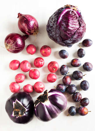 %u0421ollection of fresh purple toned vegetables on white wooden