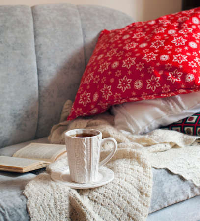 Still life interior details, cup of tea and book on the sofa with pillows
