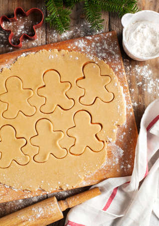 Making gingerbread cookies. Christmas baking background dough and cookie cutters. photo