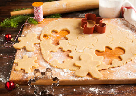 christmas baking: Making gingerbread cookies. Christmas baking background dough and cookie cutters.