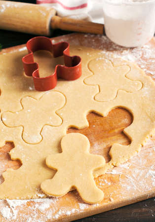 wood cutter: Making gingerbread cookies. Christmas baking background dough and cookie cutters.