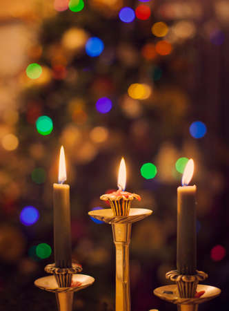 burning candles on blurring christmas lights background stock photo 34504312