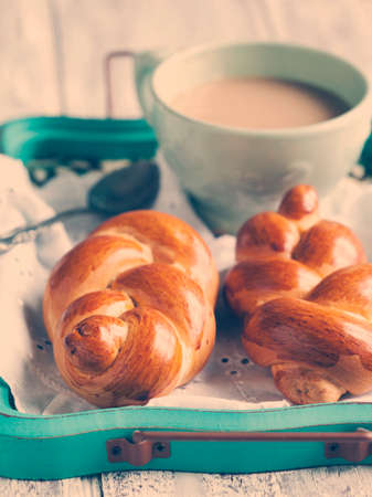 Braided buns and cup oh hot chocolate. Toned image