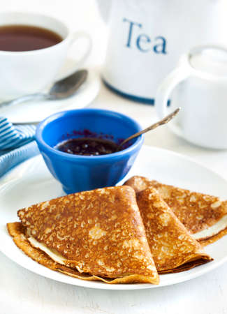 Homemade crepes folded in triangles with black currant jam and cup of tea 版權商用圖片