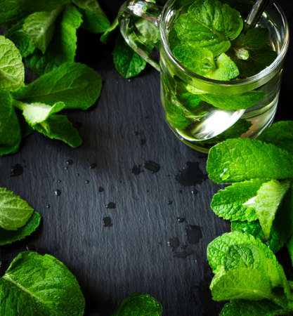 green: Mint tea and mint leaves over black background with copy space Stock Photo