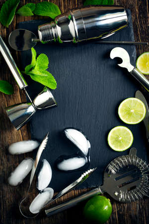 Set of bar accessories and ingredients for making a cocktails arranged on a wooden background with black board for copy space Stok Fotoğraf