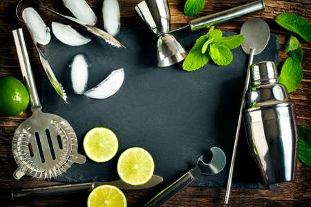cocteles de frutas: Conjunto de accesorios e ingredientes de barras para hacer unos cócteles dispuestas sobre un fondo de madera con placa de negro para el espacio de copia Foto de archivo