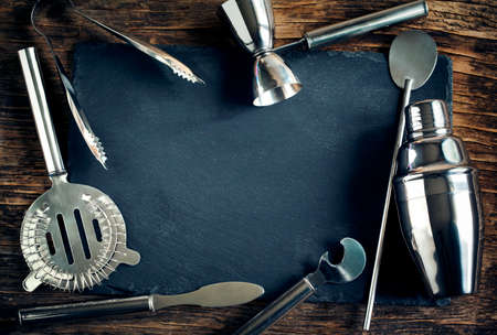 barra de bar: Conjunto de accesorios e ingredientes de barras para hacer unos c�cteles dispuestas sobre un fondo de madera con placa de negro para el espacio de copia Foto de archivo