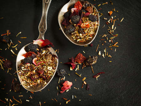 rooibos: Blueberry Bliss Rooibos Tea in spoons on black background Stock Photo