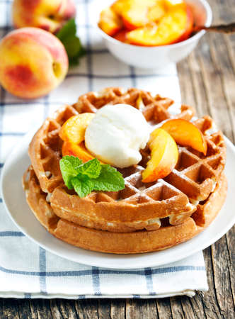Belgian waffles with ice cream and fresh peaches Stockfoto