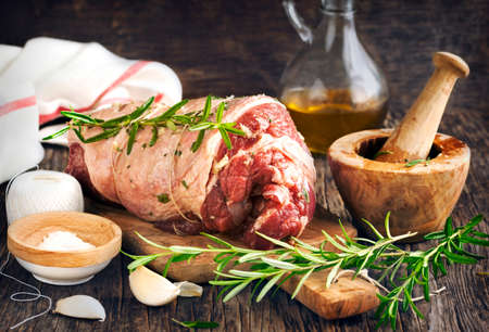 Raw boneless lamb leg with garlic and rosemary on wooden background.
