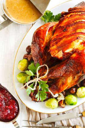 Gerösteter Truthahn mit Speck und garniert mit Kastanien und Rosenkohl. Vorbereitet für Thanksgiving oder Weihnachtsessen. Standard-Bild - 47703173