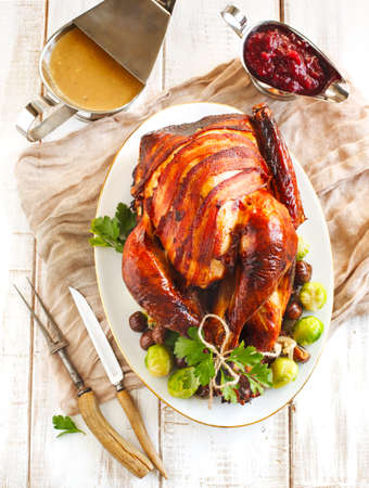 Roasted turkey with bacon and garnished with chestnuts and brussels sprouts. Prepared for Thanksgiving or Christmas dinner.